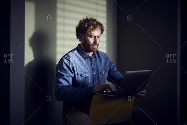 Casual businessman sitting down using laptop