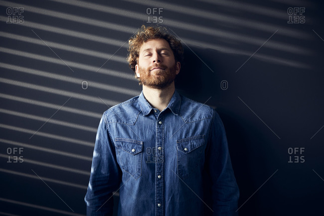 Casual businessman with closed eyes leaning against a wall