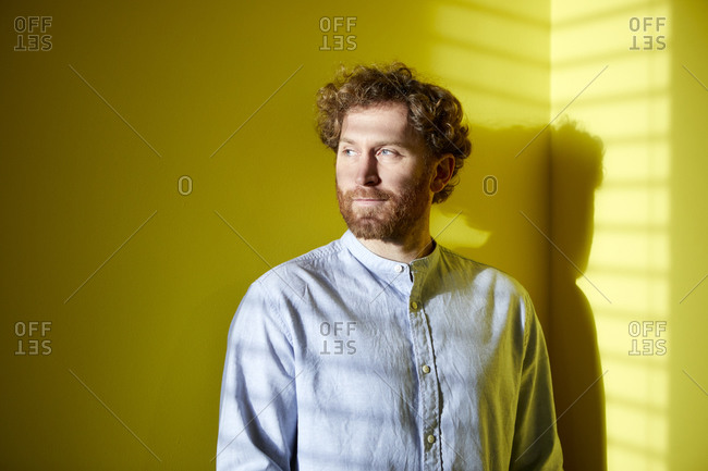 Portrait of a casual businessman at a yellow wall with light and shadow