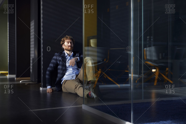 Businessman sitting on the floor in office with closed eyes