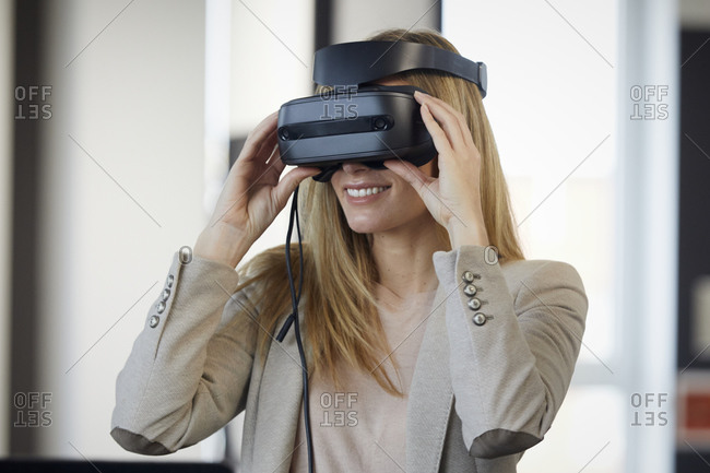 Smiling businesswoman wearing VR glasses in office