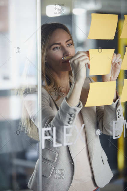 Businesswoman writing on adhesive notes on glass pane in office