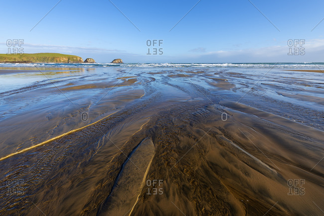 New Zealand- Otago- Coastal water flowing through sand of Tautuku Beach