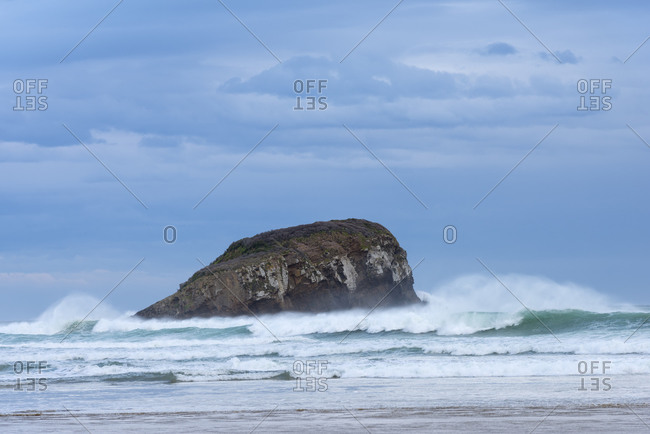 New Zealand- Otago- Ocean waves splashing against coastal stack rock