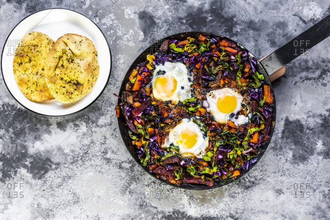 Pan of beetroot shakshuka with chard- carrots- tomatoes- red cabbage and pita bread