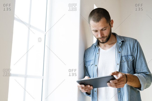 Young serious man at home looking at his tablet standing at window