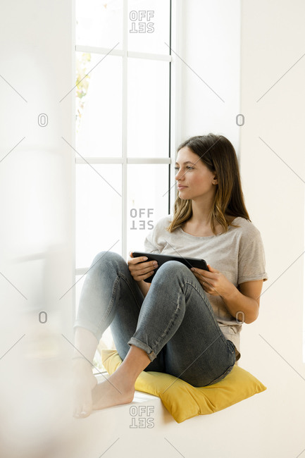 Serious young brunette woman at home sitting on window bench and holding her tablet while looking outside
