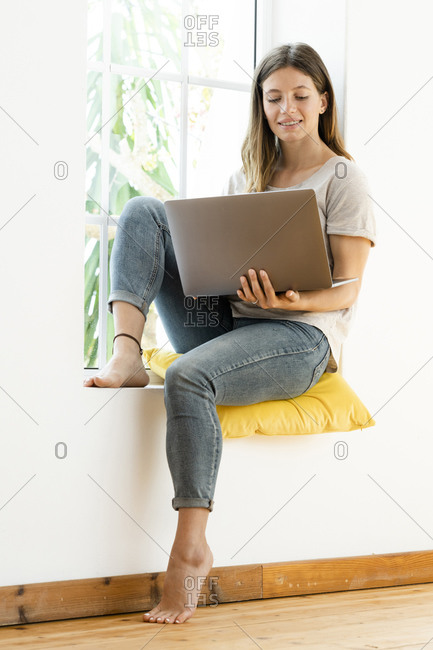 Smiling young brunette woman at home sitting on window bench and holding her laptop working in home office
