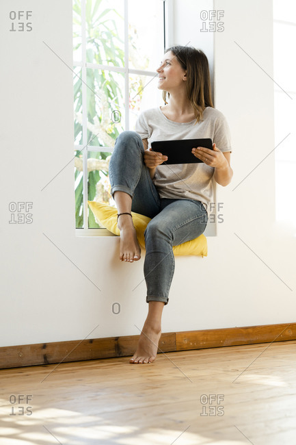 Smiling young brunette woman at home sitting on window bench and holding her tablet looking outside