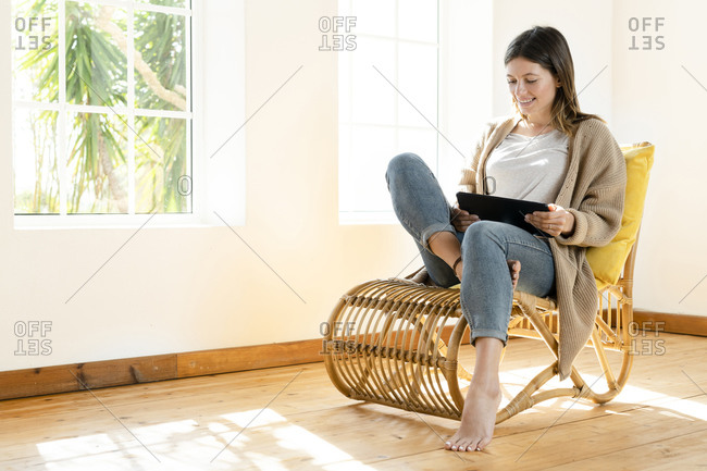 Smiling young brunette woman at home sitting in wooden armchair in front of window and looking at her tablet