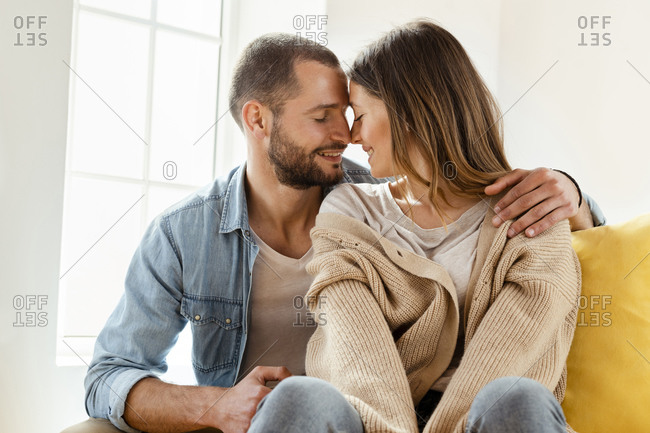 Affectionate smiling couple with closed eyes in love at home