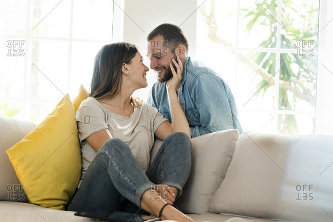 Affectionate couple in love about to kiss while relaxing at home on couch