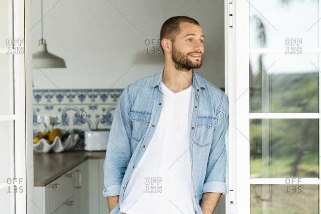 Confident young man standing in the door at home and looking outside