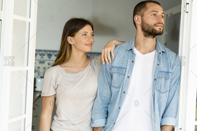 Attractive young couple standing in the door together at home and looking outside
