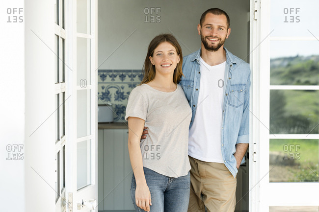 Attractive young couple standing in the door together at home and smiling