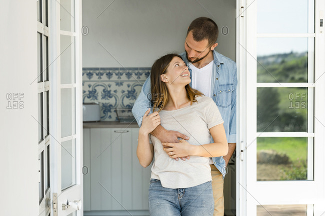 Attractive young couple standing in the door together at home and smiling at each other