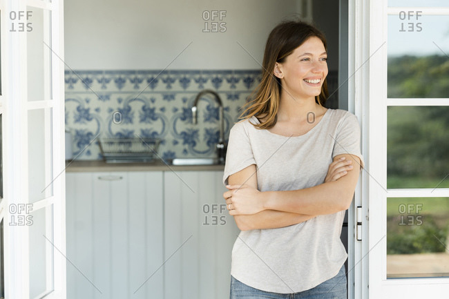 Attractive young woman standing in the door at home and smiling