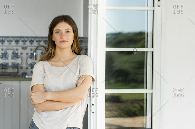 Portrait of attractive young woman standing in the door at home