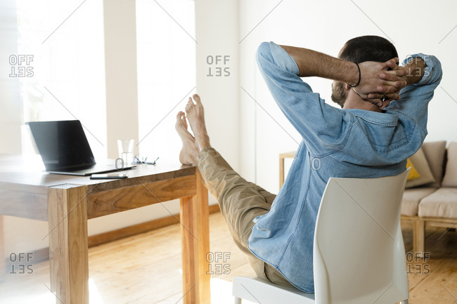 Young man at home working in home office and relaxing in modern living room with his feet on the table