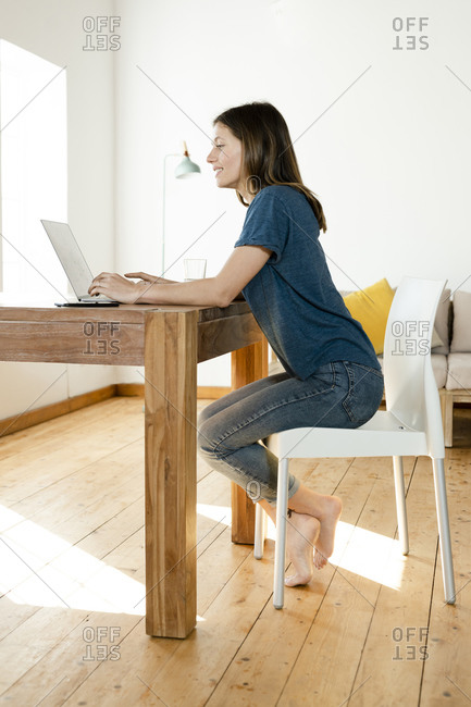 Young woman working at laptop from home in home office in modern living room