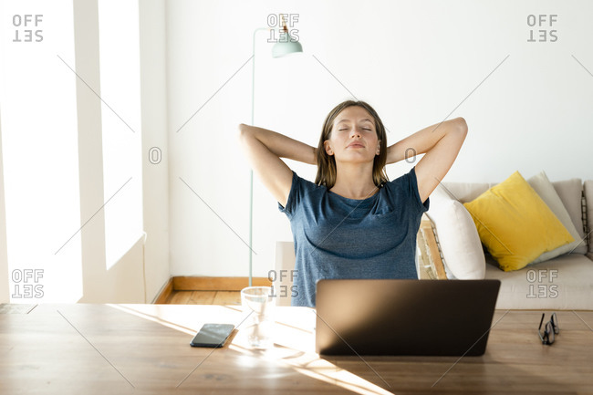 Young woman at home relaxing and having a break from working at laptop in home office