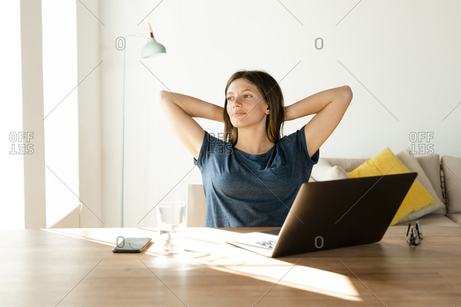 Content young woman at home having a break from working at laptop in home office