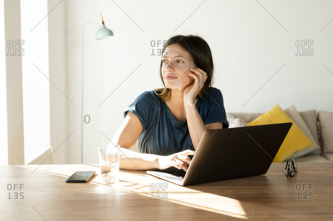Young woman at home working at laptop in home office in modern living room and looking outside