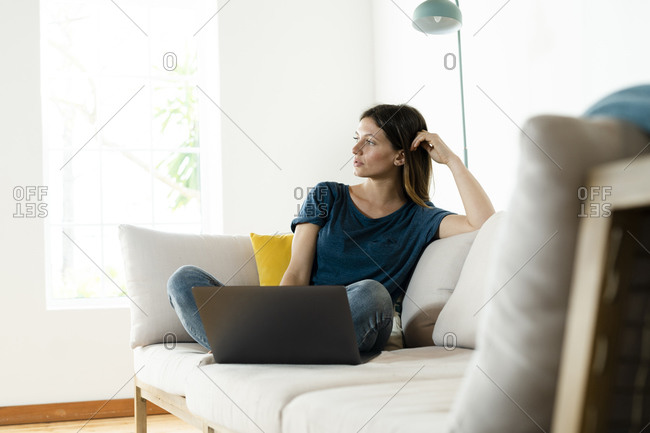 Young woman sitting on couch at home with laptop