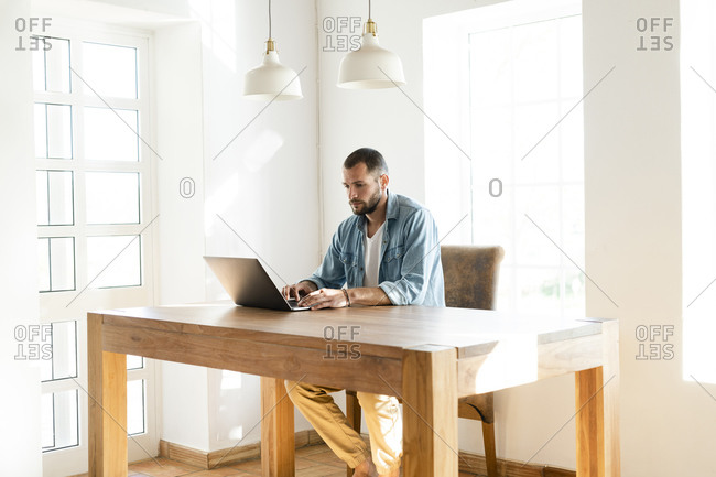 Young man at home working on his laptop in home office in modern living room