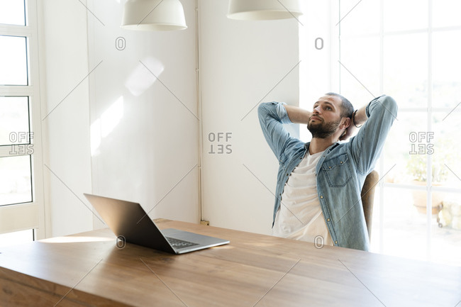 Serious young man with laptop in home office having a break