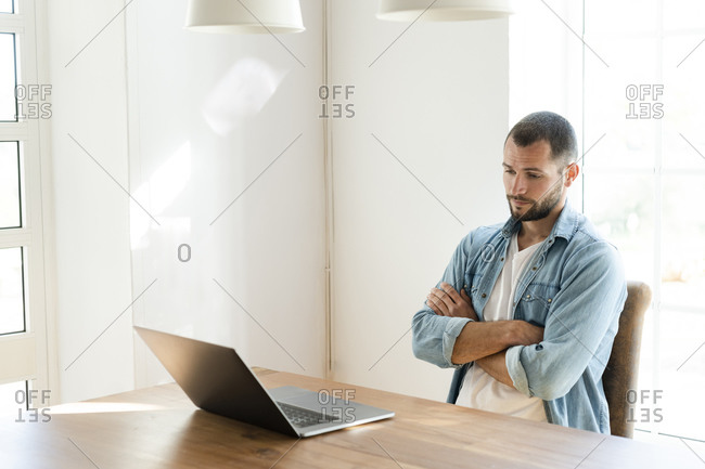 Serious young man with crossed arms at home looking at his laptop in home office