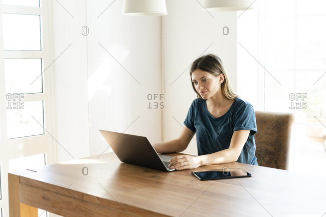 Young woman at home working on her laptop in home office