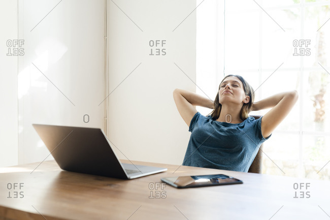 Young woman with laptop in home office having a break