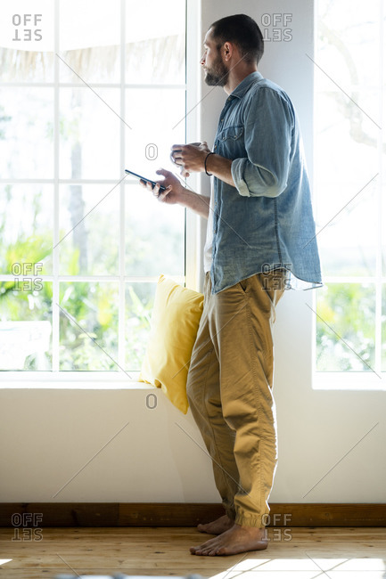Young man at home holding his smartphone and coffee mug and looking outside