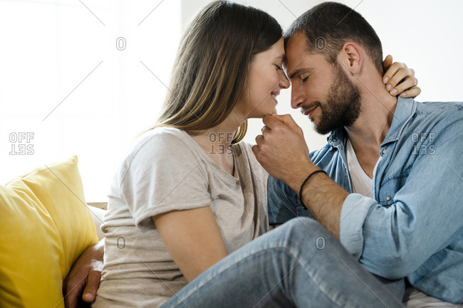 Affectionate young couple in love cuddling on couch at home