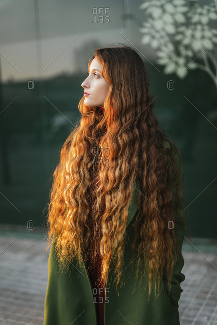 Portrait of pensive redheaded young woman looking at distance