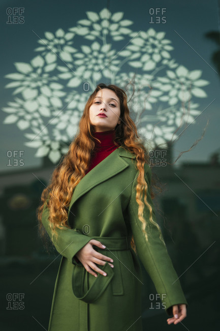 Portrait of redheaded young woman wearing fashionable green coat