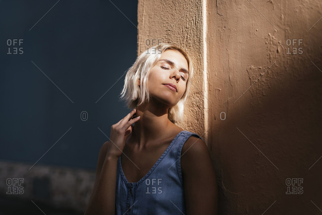 Portrait of young blond woman leaning against wall enjoying sunlight