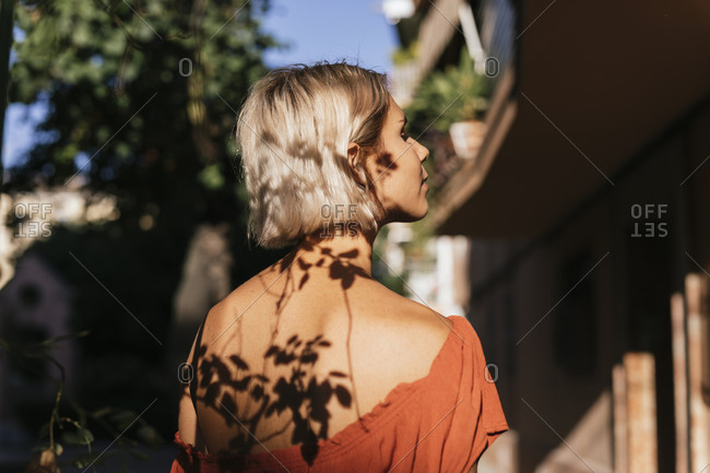 Young woman at sunlight with shadows of leaves on face and back