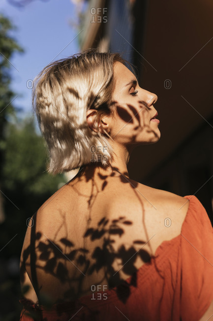 Profile of young woman with shadows of leaves on face and back