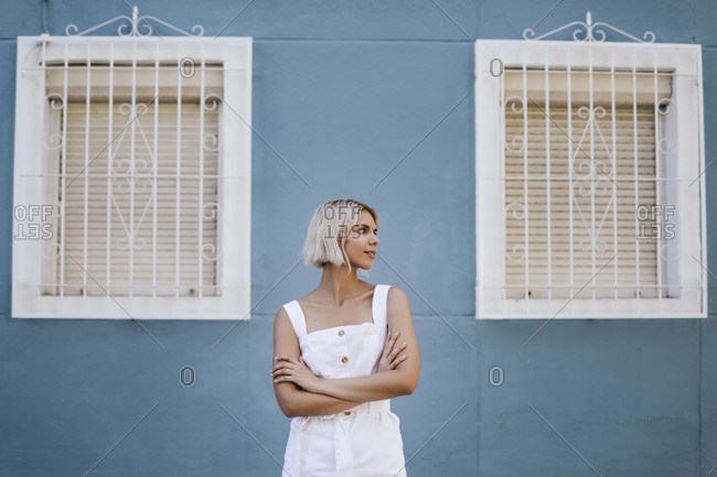 Portrait of young woman wearing white summer dress in front of blue facade