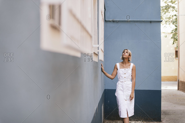Portrait of young woman wearing white summer dress looking up