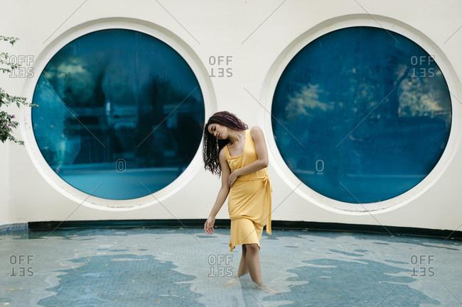 Young woman wearing yellow summer dress dancing in pool