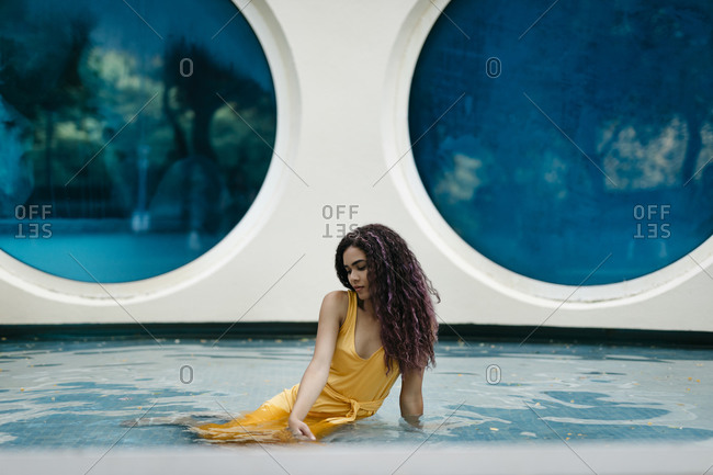 Young woman wearing yellow summer dress sitting in pool