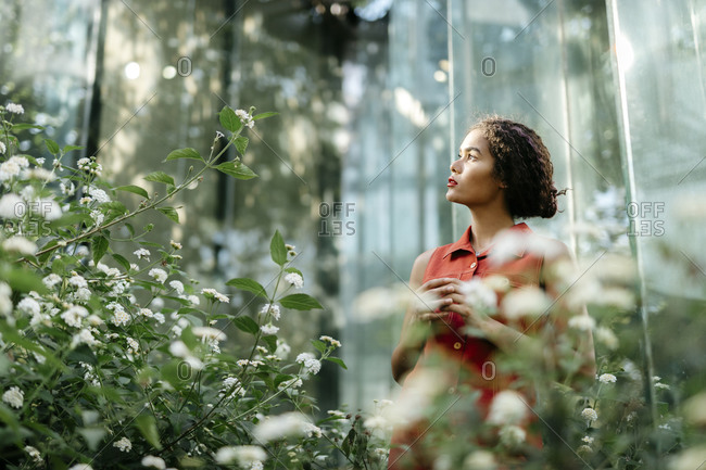 Portrait of pensive young woman standing in urban garden looking up