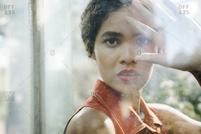 Portrait of young woman behind glass pane