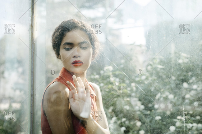 Portrait of young woman behind glass pane looking down