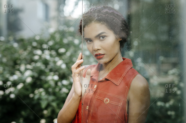 Portrait of young woman with red lips behind glass pane