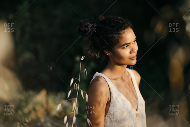 Portrait of young woman in nature watching sunset