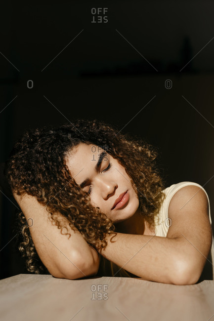 Portrait of attractive young woman leaning on a table in sunlight
